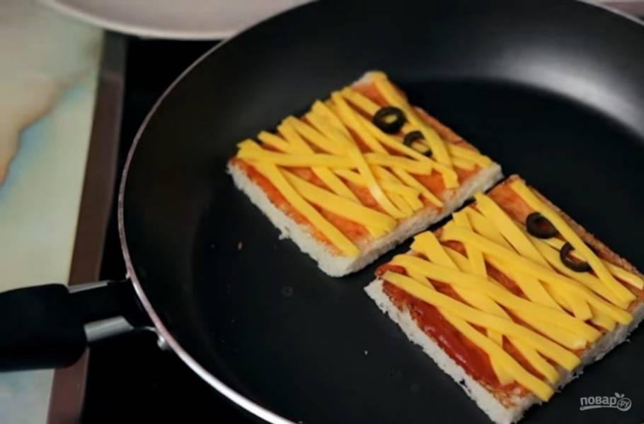 2. После этого смажьте поджаренную сторону кетчупом и аккуратно выложите нарезанный тонкими полосками сыр (в виде бинтов). Из маслин вырежьте глаза и поместите на верх ломтика хлеба. Снова поджарьте хлеб с одной стороны, чтобы сыр немного расплавился.