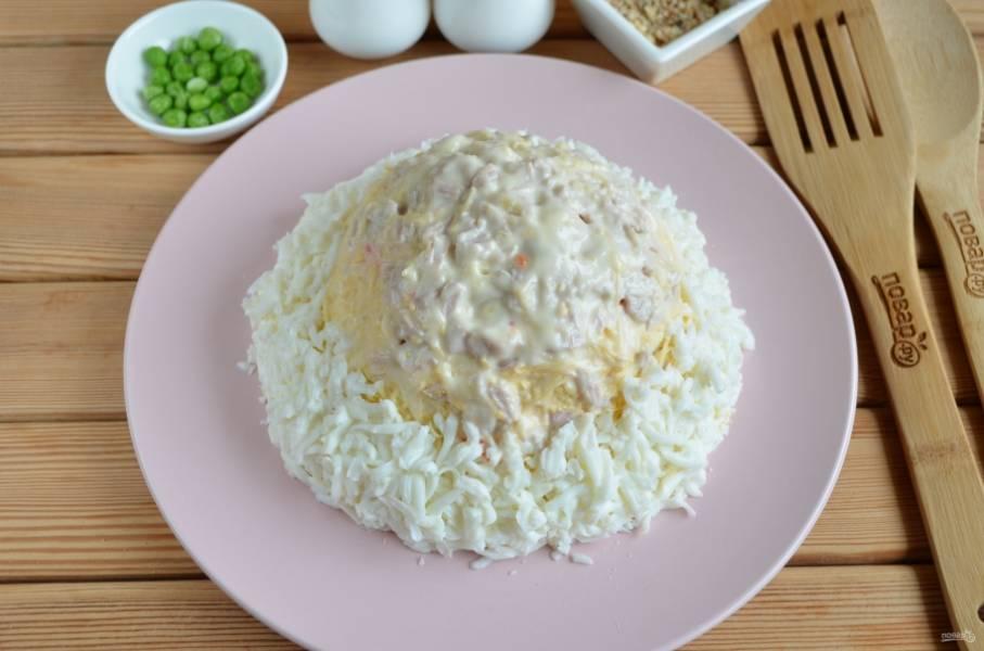 9. Далее — половина тертого сыра, оставшееся мясо. Аккуратно полностью смажьте салат майонезом. По кругу сделайте опушку из сыра, потом сверху распределите яичный белок.