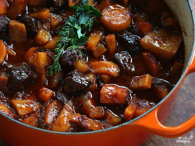 Прежде чем отправить рагу тушиться, добавьте в кастрюлю 200 миллилитров маринада с вином. Включите небольшой огонь и тушите рагу около двух часов. По необходимости доливайте воду. Нужно, чтобы говядина стала мягкой. Подавать блюдо лучше горячим в глубоких тарелках.