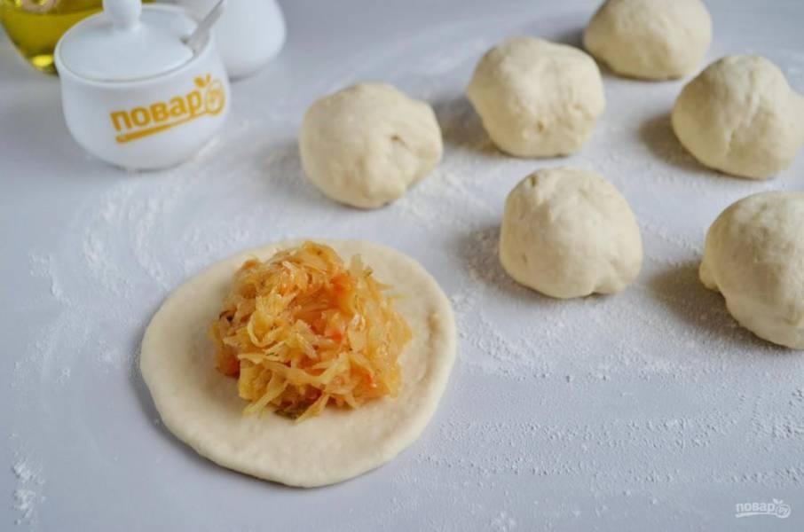 6. Разделите тесто на части, для больших пирожков 8-10 кусочков, для более маленьких 12-14 частей. Каждый комочек теста раскатайте и положите начинку.