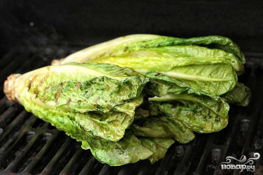 3. Обжарить салат на гриле, используя щипцы. Для этого выложить салат на решетку и держать щипцами, пока он не нагреется и слегка не обуглится. Следите, чтобы салат не пригорел. Продолжайте переворачивать его щипцами, чтобы оно равномерно поджарился со всех сторон. Это займет всего несколько минут.