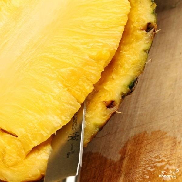 Первое, что делаем - разрезаем ананас пополам и аккуратно вырезаем мякоть из половинки ананаса. Оставляем только своеобразную лодочку из ананаса.