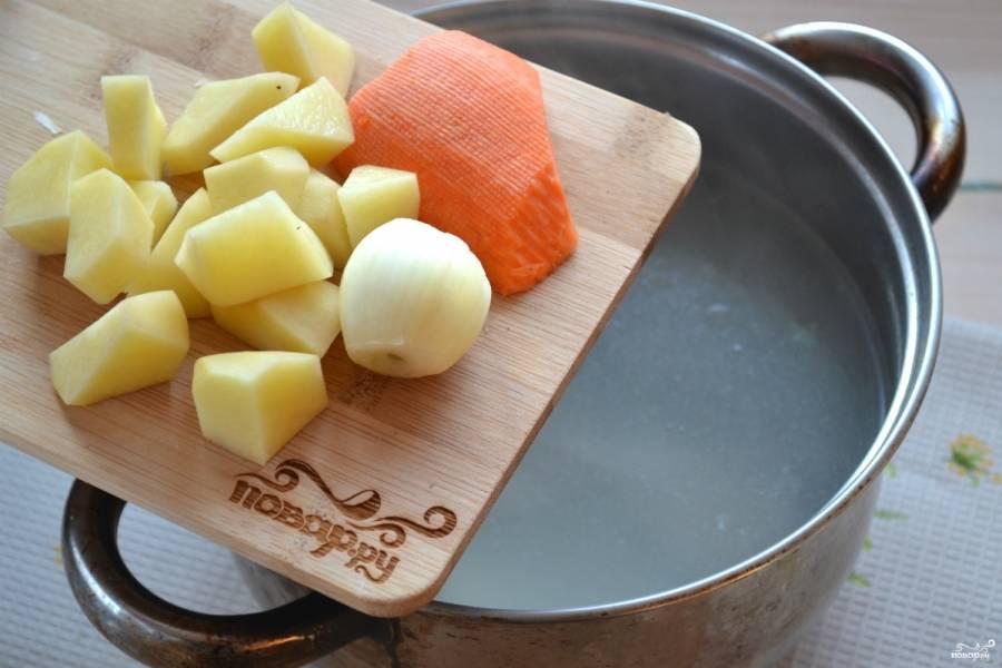 Очищенный картофель порежьте небольшими кусочками и добавьте в бульон. Туда же отправьте целую луковицу и морковку. Ни резать, ни натирать на терке их не нужно, они необходимы только для цвета и аромата, а конце их следует вынуть.