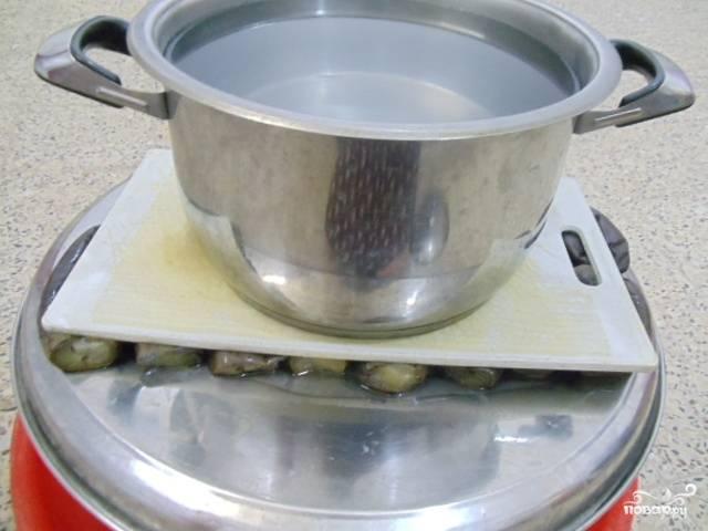 Достанем баклажаны из воды и положим под небольшой гнет на пару-тройку часов — пока не стечет вся горечь и лишняя влага.