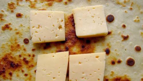 3. По центру каждого блина выкладываем несколько кусочков сыра, сворачиваем блин тугим конвертиком.