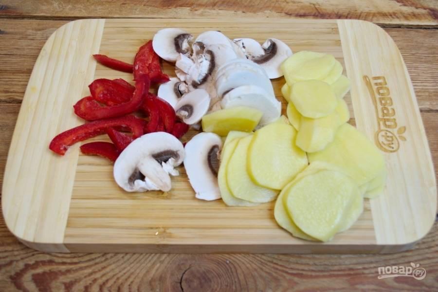 Рыбу посолите и поперчите по вкусу. Смажьте слегка рыбку майонезом. Отдельно нарежьте картофель кружочками (тонко), болгарский перец — полукольцами, репчатый лук — полукольцами. Шампиньоны нарежьте на пластинки.