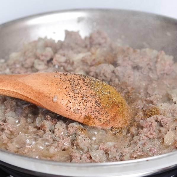 Сразу же добавьте нарезанный лук. Добавьте специи и посолите. Хорошо помешайте. После 5 минут обжарки, добавьте воды и уменьшите огонь до средне-низкого уровня. Накройте крышкой и готовьте в течении 20 минут.