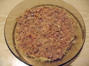 Первым делом нужно отварить картофель, морковь и яйца. Отваренные продукты остудить и почистить. На мелкой тёрке натереть картошку, морковку, белки, желтки и сыр (всё в отдельных мисочках или тарелках). В салатницу выложить рыбу с маслом и размять вилкой по всей поверхности дна посуды. Сверху смазать небольшим количеством майонеза.