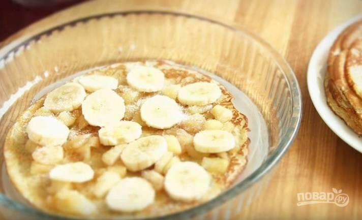 6. Форму для выпечки смажьте сливочным маслом. На блинчик выложите яблочную начинку, колечки бананов и присыпьте немного сахаром. Чередуйте так все слои. Накройте форму фольгой и выпекайте 20 минут при температуре 180 градусов.