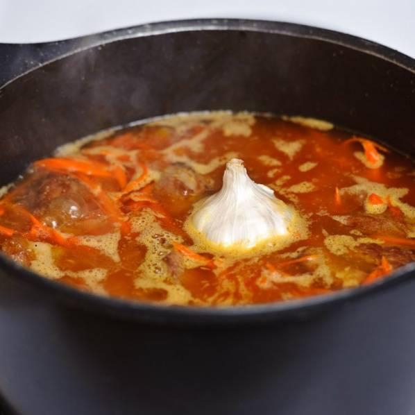 Когда вода хорошо нагреется (не закипит) нужно добавить головку чеснока. Варить на среднем огне в течении 1 часа. Промойте рис.