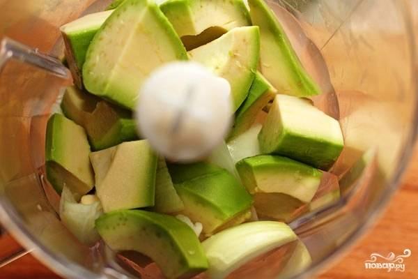 Кладем в блендер кусочки авокадо и половину очищенной луковицы. Измельчаем до однородности.