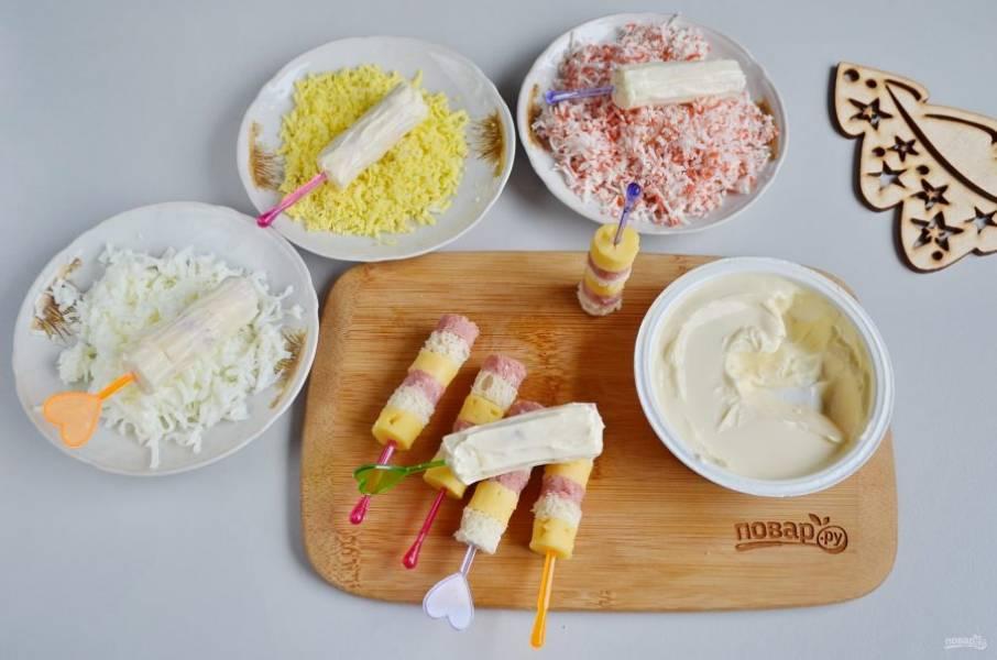 Каждый бутербродик тщательно смажьте сыром со всех сторон. Обваляйте канапе в разных посыпках: в желтке, белке или крабовых палочках.