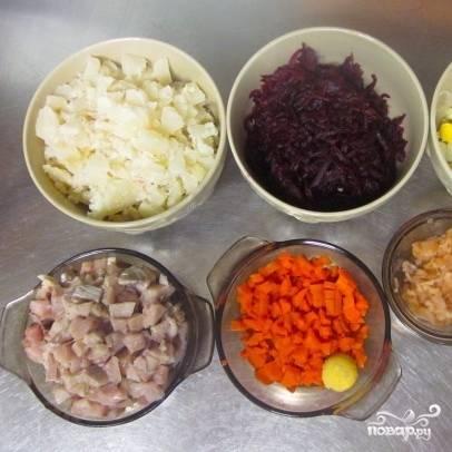 Теперь занимаемся измельчением. Лук нарезаем мелко, свеклу и яблоко (очищенное от семян и кожуры) натираем на крупной терке (выделившуюся в процессе натирания жидкость необходимо слить). Яйца, картофель, морковь и селедку нарезаем кубиками. Немножко яичного желтка можно оставить для украшения готового салата.
