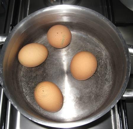3. Для разнообразия в рецепт приготовления капустных пирожков жареных можно добавить отварные яйца. Их нужно залить холодной водой и отправить на огонь.