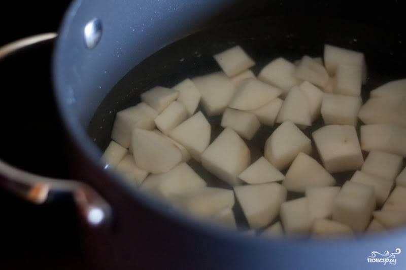 Как только вы закинули овощи в кастрюлю, залейте в отдельной кастрюльке картофель водой. Доведите до кипения, уменьшите огонь и варите, пока он не станет мягким.