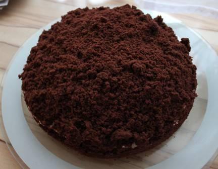 Часть коржа, которую мы вынули из серединки, измельчаем в крошки и густо посыпаем ими торт. Ставим торт в холодильник часа на 2.