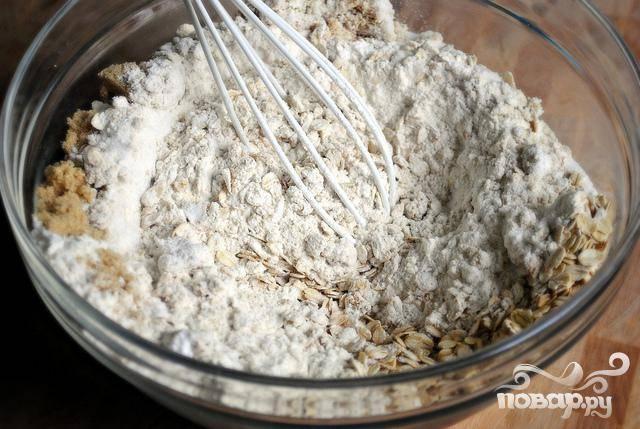 1. Разогреть духовку до 175 градусов. В большой миске смешать вместе овсяные хлопья, муку, сахар, разрыхлитель, соду и соль.