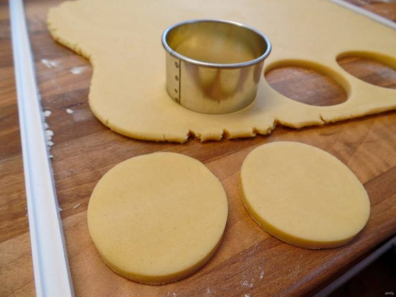 6.Достаньте охлажденное тесто, раскатайте его в пласт около 0,8-1 см в толщину, затем круглой формочкой или стаканом вырежьте кружочки (чтобы поместились в формы для кексов).