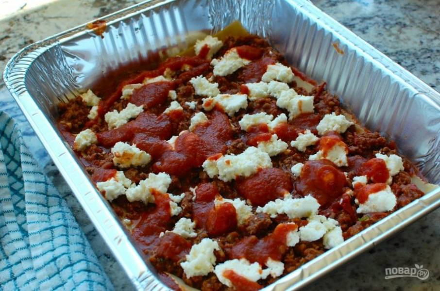 15.Добавьте половину сырной начинки и еще в каждую форму по 2 столовые ложки соуса.