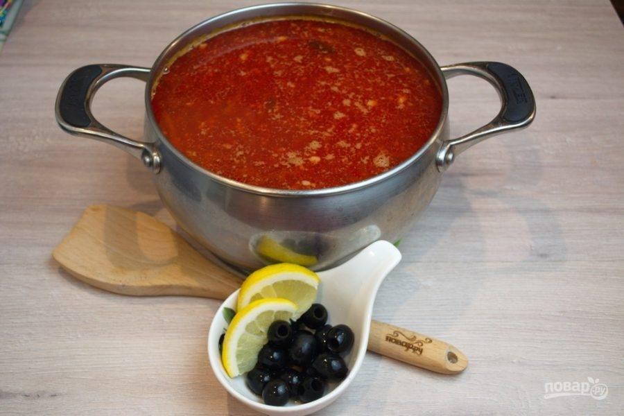 """Когда мясо сварится, извлеките его из бульона. Нарежьте кубиком и верните в бульон. Также в бульон добавьте томатную зажарку. Варите 10-15 минут. Вкусы """"подружатся"""", солянка приобретет устойчивый вкус. Влейте в солянку огурцы вместе с водой, в которой они варились. Перемешайте. Теперь можно приправить солянку специями, солью. Добавьте оливки, маслины, лимонные дольки."""