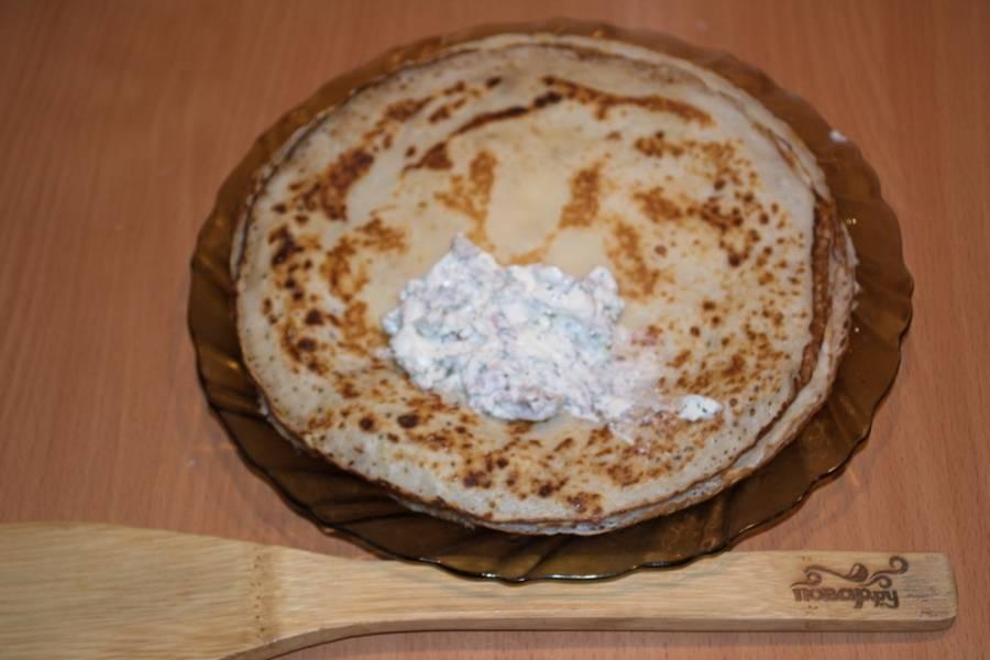 Привычным способом обжарьте блинчики. Крем сыр поместите в миску. Добавьте нарезанную отварную индейку. Добавьте соль, специи и сметану. Перемешайте. Полученной массой наполните блинчики и сверните конвертиком.  В начинку можно добавить зелень.