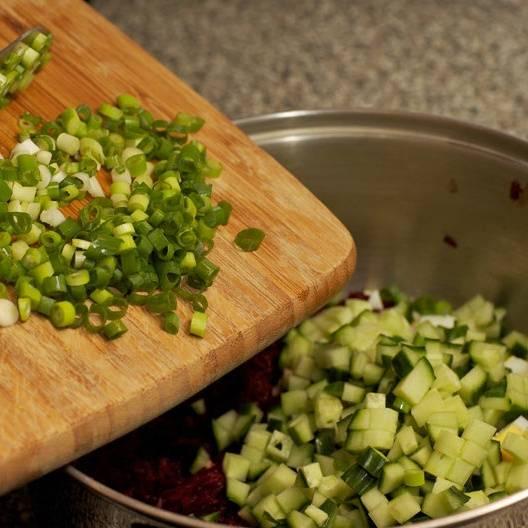 Нарезать огурцы и зеленый лук. Добавить в кастрюлю.