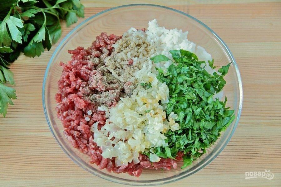 Тем временем к фаршу добавьте обжаренный на сливочном масле репчатый лук, отваренный до полуготовности рис, измельченную зелень, соль и перец по вкусу.