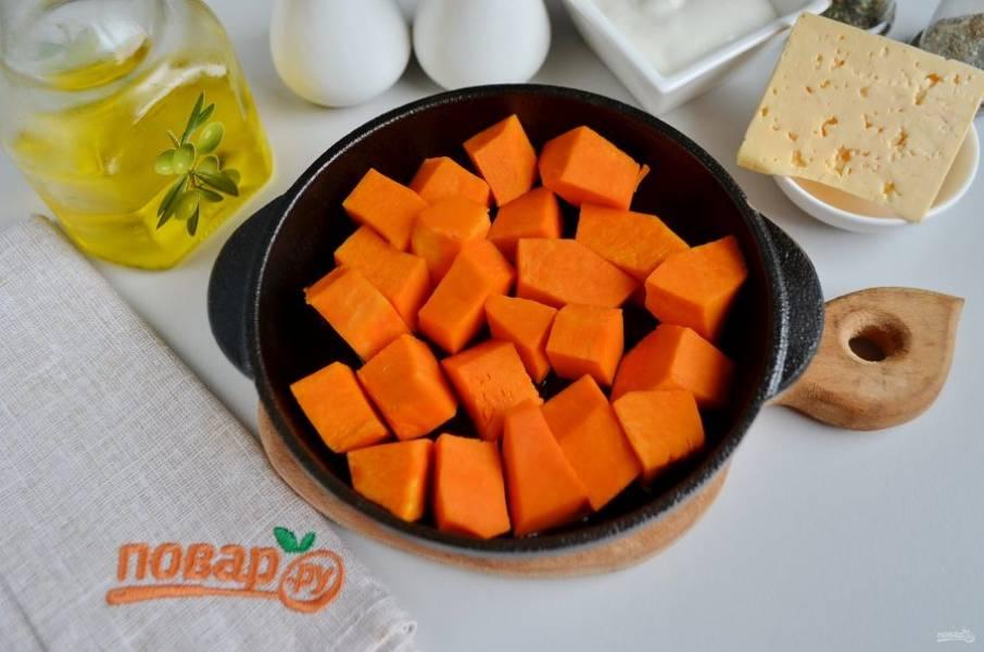 Тыкву порежьте на небольшие кубики. Масло растительное разогрейте и добавьте тыкву.
