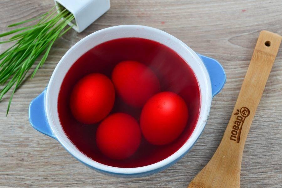 Вареные яйца сложите в глубокую миску. Содержимое кастрюли процедите и залейте яйца красивой розовой жидкостью. Оставьте так яйца на 30 минут, если есть время, можно оставить на ночь, тогда яйца получатся бордовыми.