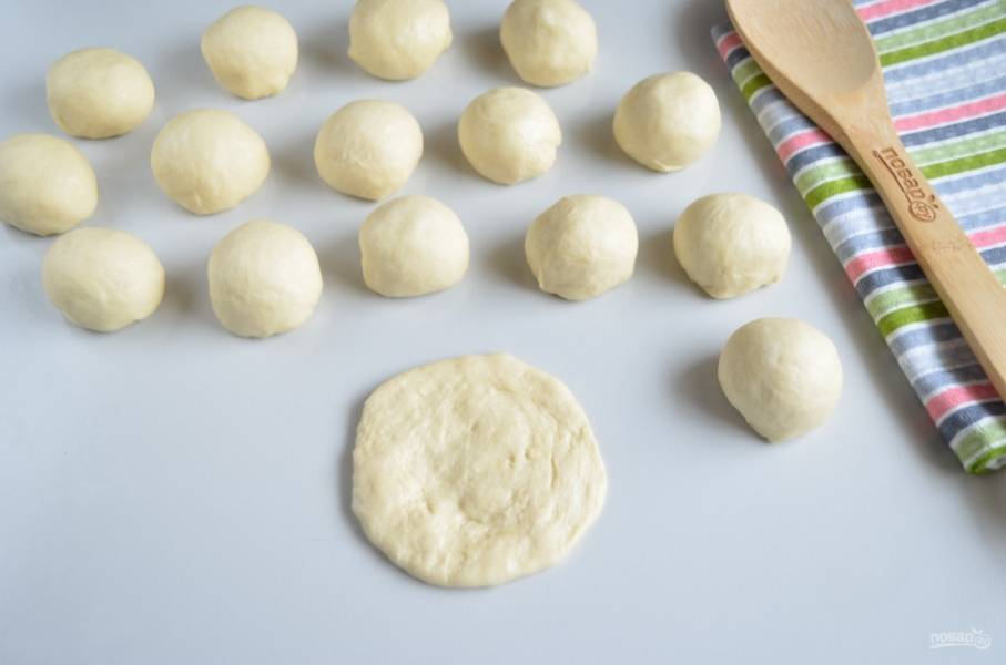 Спустя час осадите тесто руками, разделите на небольшие шарики размером чуть больше грецкого ореха. Муку не нужно использовать, смажьте стол маслом, чтобы не тесто не прилипало. Приступаем к лепке. Шарик теста пальцами расплющите по столу.