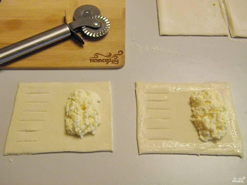 Порежьте тесто, не раскатывая на прямоугольники. С одной стороны сделайте красивые надрезы. Весь периметр смажьте белком, чтобы лучше склеился край слойки. В центр выложите по столовой ложке творога.