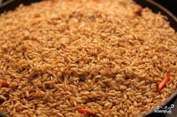 9. Аккуратно достаньте чеснок и перец, но не выбрасывайте, они еще пригодятся. Всыпьте рис. Важно не перемешивать!