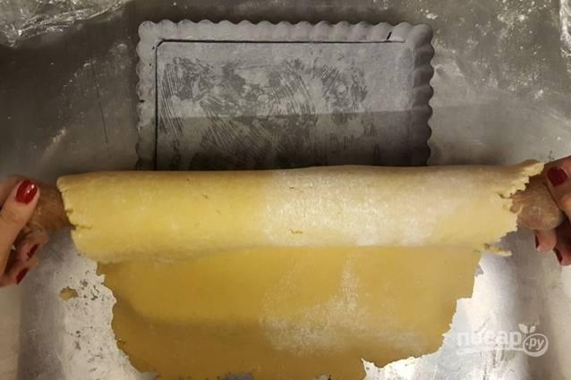 4. Раскатайте скалкой тесто в пласт толщиной 1 см, на посыпанной мукой рабочей поверхности, и разделите его пополам. 1-я часть будет основанием пирога, а 2-ую часть оставьте для украшения - полосок, звездочек и т.д. Форму для выпечки смажьте маслом, посыпьте мукой и перенесите пласт теста с помощью скалки.