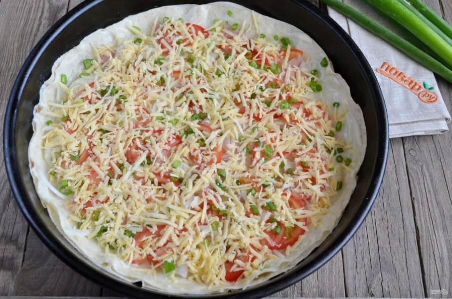Распределите тертый сыр по всей поверхности пиццы. Прогрейте духовку до 200 градусов и поставьте пиццу на 12-15 минут.
