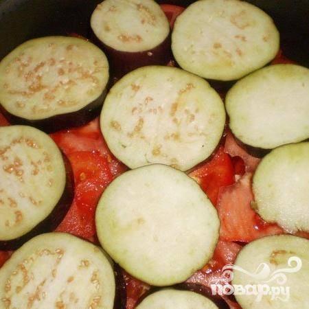 3. Очищаем морковь и нарезаем ее кружочками. На лук выкладываем слой моркови. Промываем помидоры, колечками их нарезаем и на слой моркови выкладываем. Толщиной полтора-два сантиметра нарезаем кружочками баклажаны, посыпаем немного солью, промываем, обсушим, и выкладываем на помидоры.