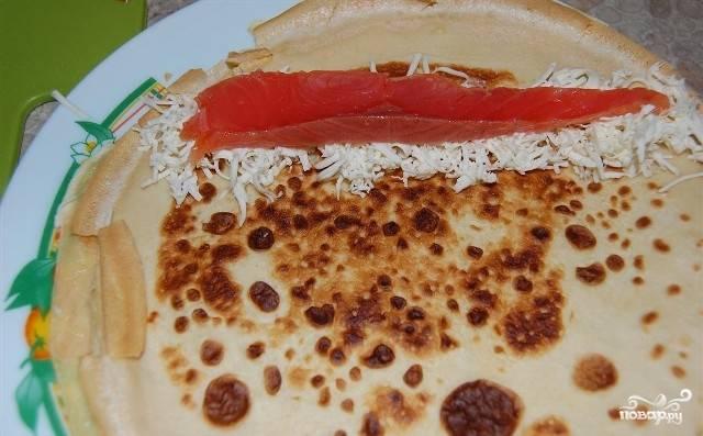 На сыр выкладываем кусочек семги. Если у вас не получилось нарезать рыбу тонкими пластинками - не беда. Ее можно нарезать более мелко и точно так же выложить на сыр.