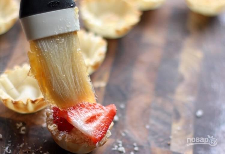 4.Смажьте сверху клубнику абрикосовым джемом, измельчите фундук и посыпьте им каждую тарталетку.