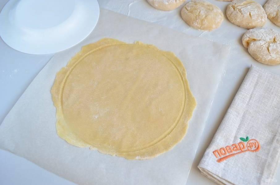 Из раскатанных пластов теста нужно вырезать круглые коржи. В качестве контура можно использовать подходящую по диаметру тарелку. Обрезки теста не выбрасываем - они нам еще будут нужны. Вообще, раскатывать это тесто нужно быстро - оно очень быстро твердеет и теряет эластичность.