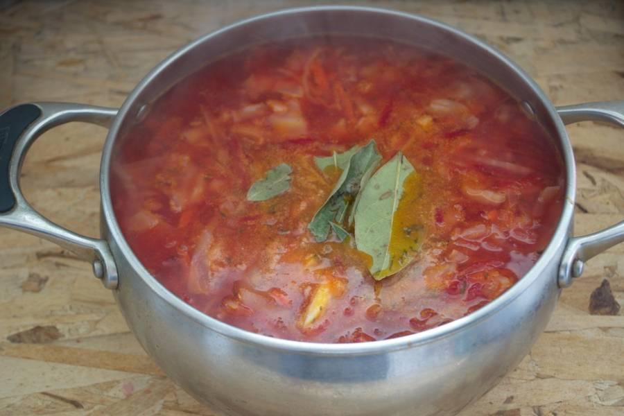 Когда капуста станет мягче, добавьте зажарку в борщ.  Перемешайте. Варите до готовности овощей. В самом конце добавьте лавровый лист. За минуту до выключения измельчите чеснок и добавьте в борщ.