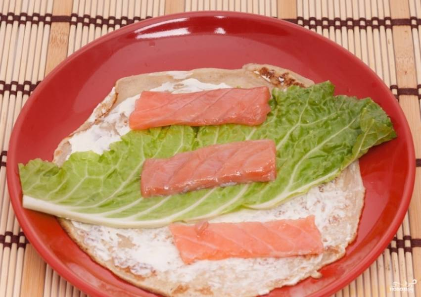 2. Каждый блин смажем сыром, выкладываем кусочек капустного листа и немного рыбы. Сворачиваем рулетом.