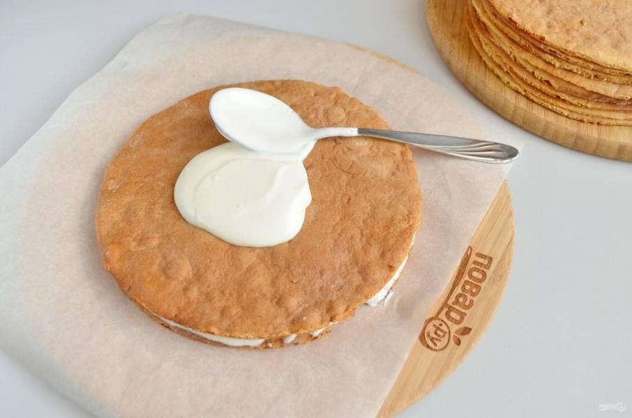 Формируем торт. На большую плоскую тарелку кладем первый корж (желательно - самый ровный, ведь он служит основанием всей конструкции) и щедро смазываем его кремом.