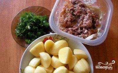 Картофель нарезаем довольно большими кусочками, тушенку достаем из банки в удобную посуду и разминаем вилкой, чтоб не было комочков,  заем мелко рубим зелень.
