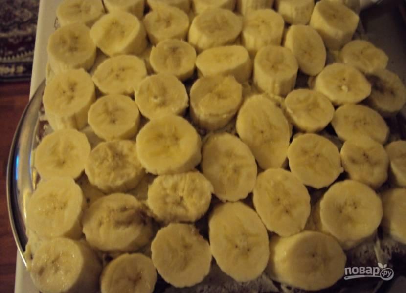 7. Намажьте половиной крема наш корж. Нарежьте банан колечками толщиной около сантиметра и выложите на крем. Затем смажьте оставшимся кремом.