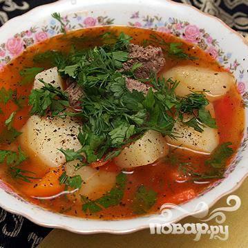 5. В средней сковороде нагреть сливочное масло. Добавить томатную пасту (или два больших помидора), измельченный чеснок и обжарить. Добавить томатную смесь в суп. Приправить суп солью и черным молотым перцем по вкусу. Перед подачей на стол добавить в суп мелко нарезанную петрушку, кинзу и укроп.