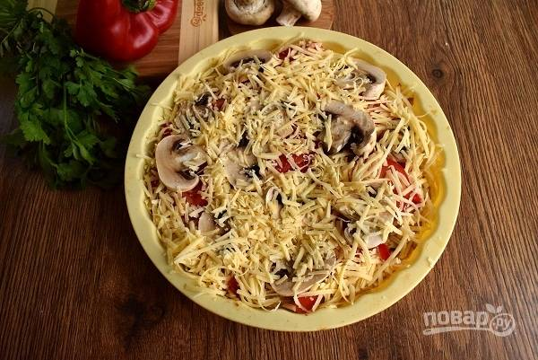 """Смажьте готовый """"корж"""" йогуртом и томатным соусом, выложите нарезанные овощи и грибы, сверху посыпьте сыром. Запекайте в духовке в течение 10-15 минут до румяной корочки сыра."""