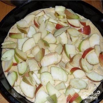 4.Форму для запекания смазать маслом и вылить в него половину приготовленного теста. Яблоки вымыть, удалить сердцевину и нарезать тонкими дольками. Выложить яблоки на тесто.