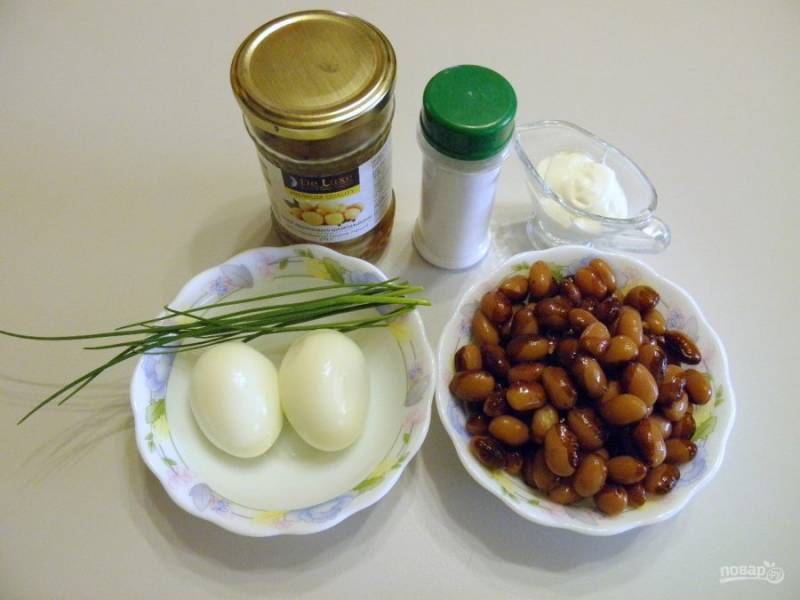 1. Подготовьте продукты для салата. Отварите яйца вкрутую, остудите их и очистите от скорлупы. Консервированную фасоль промойте кипяченой водой, откиньте на сито на пару минут, чтобы стекла вода.