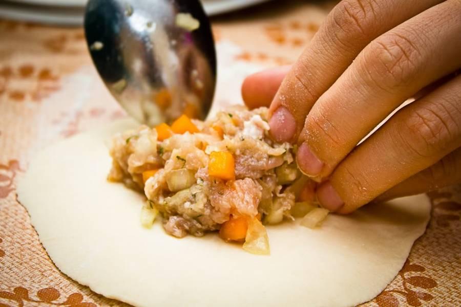 5. Выложите в центр начинку. Не жалейте: ее должно быть довольно много, тогда манты с тыквой и мясом по-узбекски в домашних условиях будут по-настоящему сочными и вкусными.