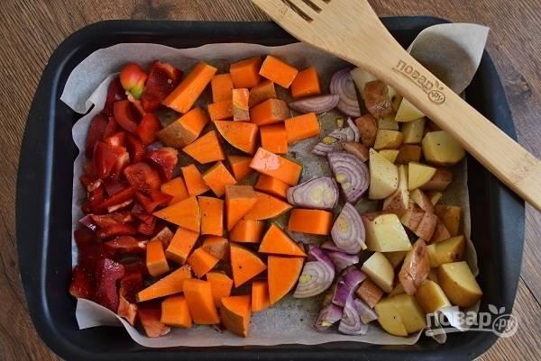 Все овощи, кроме чеснока, нарежьте крупными кусочками, разложите на пергамент в форму для запекания. Полейте оливковым маслом, посолите и поперчите по вкусу, накройте пергаментом. Запекайте в духовке в течение 30-35 минут до мягкости овощей.