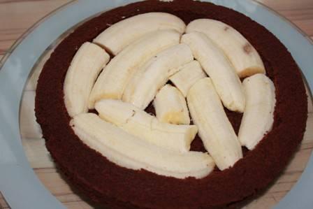 Смазываем дно формы маслом и выливаем в нее все тесто. Выпекаем корж в разогретой до 180 градусов духовке минут 30. Из остывшего коржа вынимаем серединку, оставив бортики. В получившуюся выемку укладываем очищенные бананы.